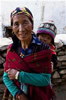 A grandmother holds walk pass the village, holding her grandson in traditional style.