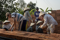 Workers load finished bricks onto waiting trucks